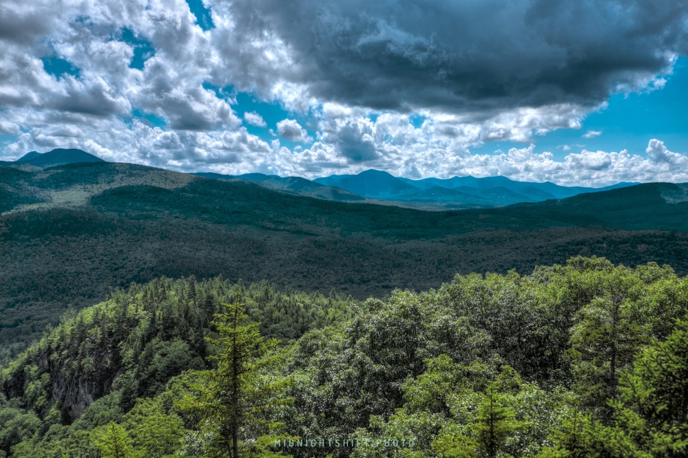 A looming rain cloud sits above the boulder loop trail in the white mountains of